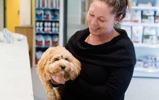 Woman holding and smiling at brown dog